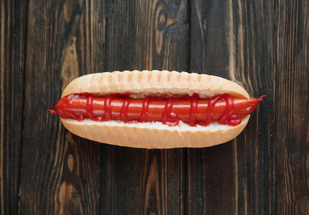 Hot dog con salsiccia affumicata sul legno scuro dello sfondo.foto con copia spazio.