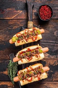 Hot dog completamente caricati con pancetta fritta, cipolla e cetrioli sottaceto. fondo in legno scuro. vista dall'alto.