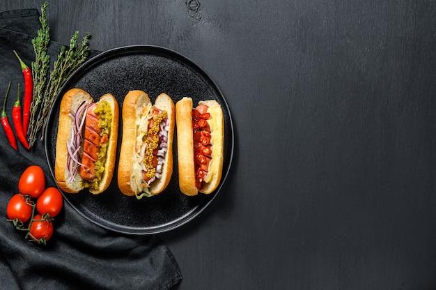 Hot dog con condimenti assortiti. deliziosi hot dog con salsicce di maiale e manzo. sfondo nero