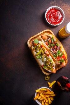 Hot dog con diversi condimenti piccanti, sfondo scuro con spazio copia, verticale