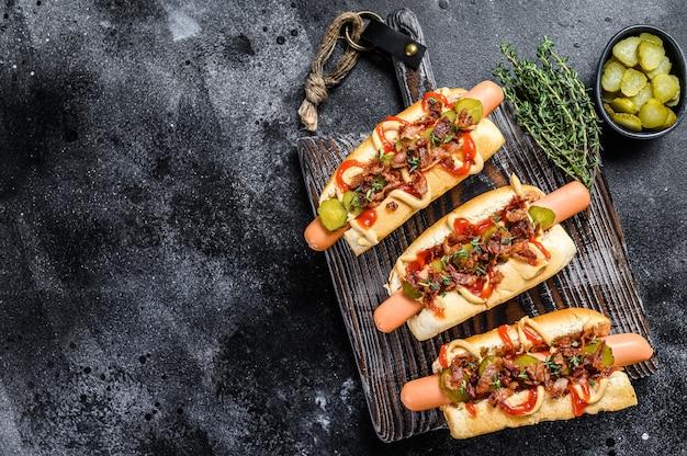 Hot dog con diversi condimenti. fondo in legno scuro. vista dall'alto. copia spazio.