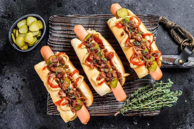 Hot dog con diversi condimenti. fondo in legno scuro. vista dall'alto.