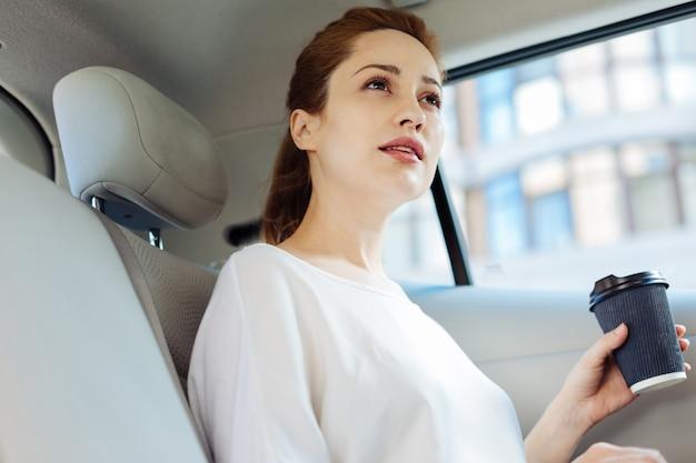 Bevanda calda. riflessivo bella donna d'affari intelligente seduto in macchina e bere il caffè mentre si va a lavorare