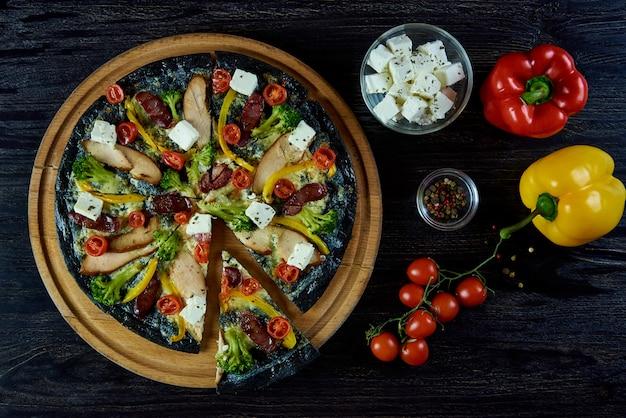 Pizza italiana deliziosa saporita calda su pasta nera con carne, verdure, formaggio e spezie