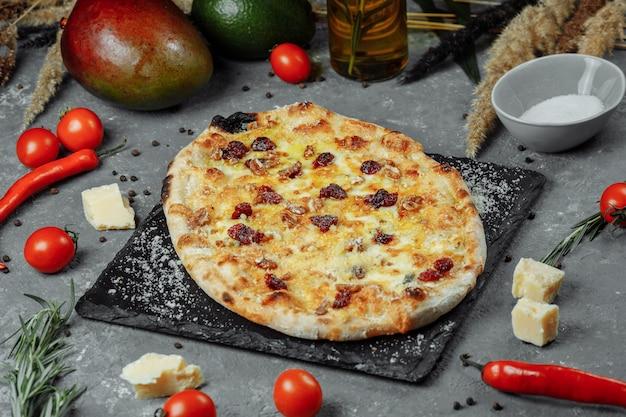 Hot quattro formaggi deliziosa pizza americana fatta in casa rustica con crosta spessa sulla tavola nera