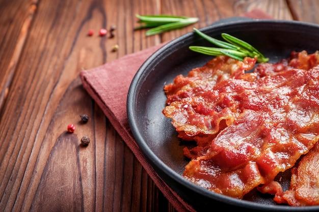 Fette di pancetta croccante fritte calde e rametti di rosmarino in padella su legno