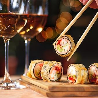 Rotolo di sushi fritto caldo con salmone e vino. menu di sushi. cibo giapponese. rotolo di sushi fritto caldo