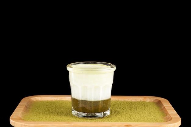 Verde caldo matcha latte con latte di mandorle su un vassoio di bambù che serve isolato su uno sfondo nero. messa a fuoco selettiva, copia dello spazio.