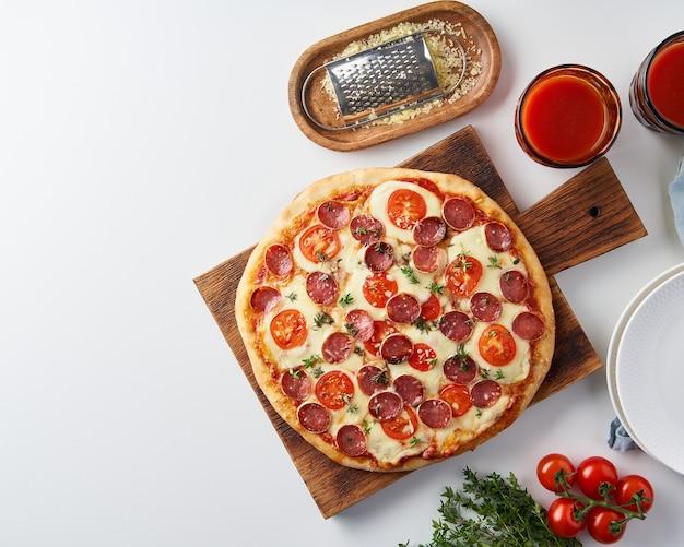 Pizza ai peperoni italiana fatta in casa calda con salame, mozzarella sul tavolo bianco, cena rustica con salsiccia e pomodori, vista dall'alto, spazio di copia