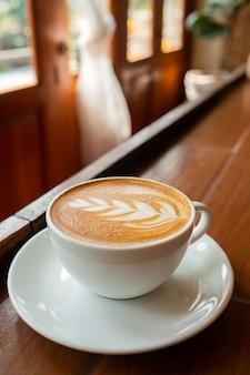 Caffè caldo latte art sul tavolo di legno, tempo di relax