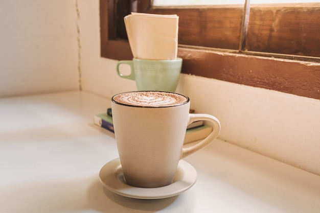 Caffè latte caldo servito in tazza bianca sul tavolo al mattino