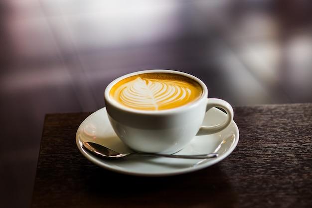 Caffè caldo del latte sulla fine della tabella in su