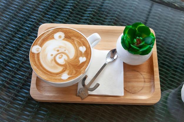 Caffè caldo del latte in tazza bianca e cucchiaio sul tavolo.