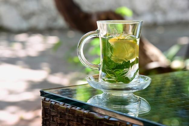 Tè caldo alla menta con foglie di menta piperita fresca e limone in una tazza di vetro.