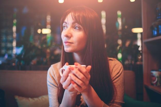 Tazza calda di tè con le mani della donna. bella femmina con una tazza di caffè al ristorante. ragazza dai capelli rossi