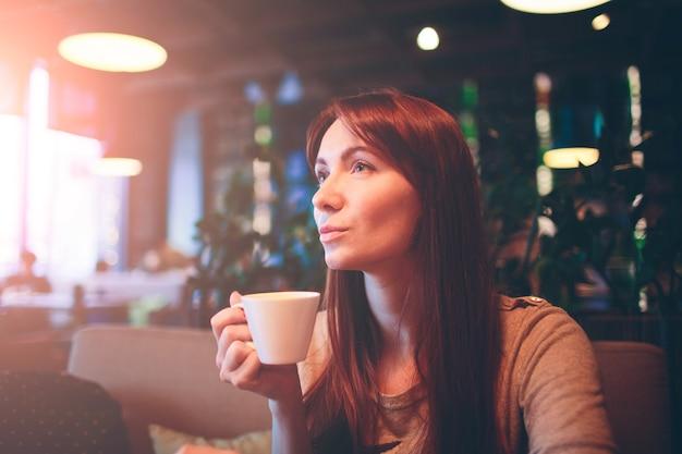 Tazza calda di tè con le mani della donna. bella femmina con una tazza di caffè al ristorante
