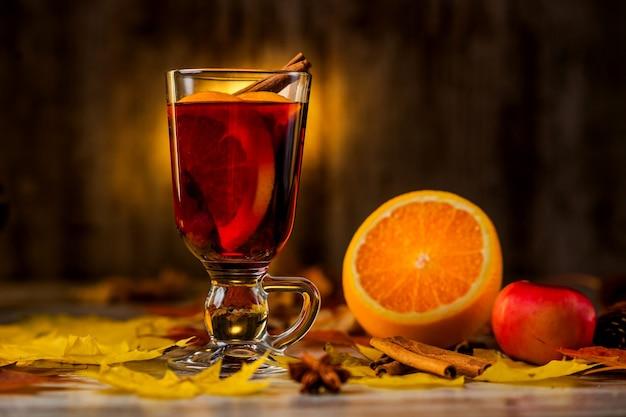 Vin brulè caldo. sulla superficie autunnale. arancia cannella vino rosso nel bicchiere. alcol. foglie di autunno rosso giallo. sulla superficie scura di legno.
