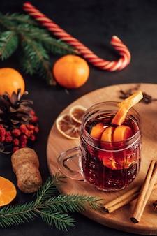 Vin brulé caldo in tazza di vetro su uno sfondo scuro. bevanda calda di natale con spezie e frutta.