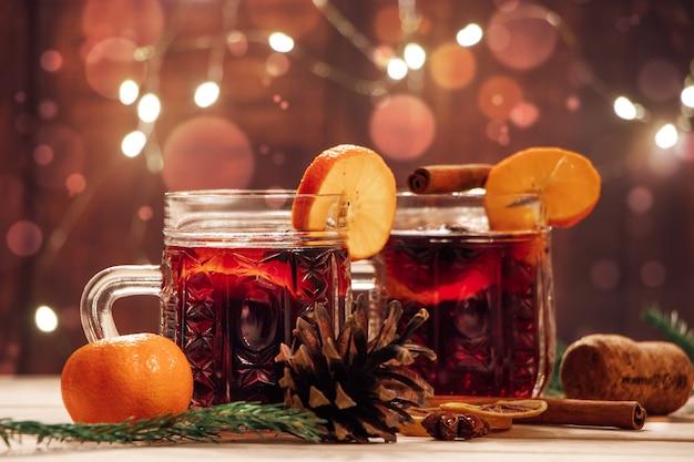 Vin brulè caldo con frutta e spezie su un tavolo di legno. bevanda per le vacanze di riscaldamento invernale.