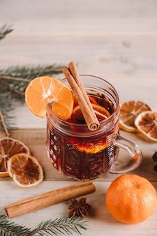 Vin brulè caldo con spezie in tazza di vetro su uno sfondo di legno. bevanda riscaldante di natale.