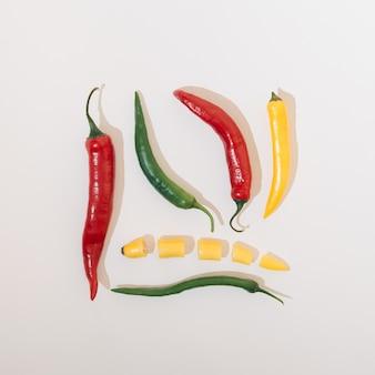 Verdure di peperoncino in diversi colori disposti in una forma quadrata su uno sfondo bianco. concetto di cibo