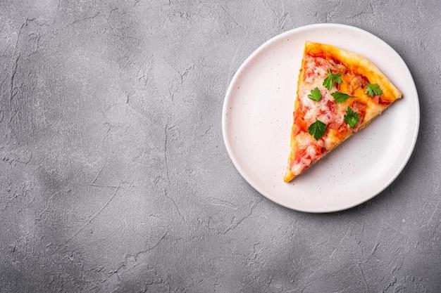 Fetta di pizza calda con mozzarella, prosciutto, pomodoro e prezzemolo sulla piastra