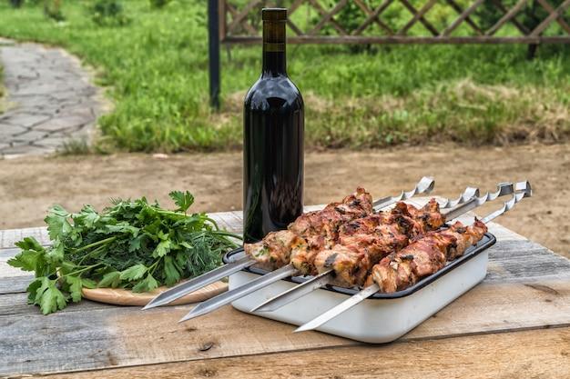 Kebab di maiale caldo, grigliato su spiedini, una bottiglia di vino rosso ed erbe su un vecchio tavolo di legno, in estate.