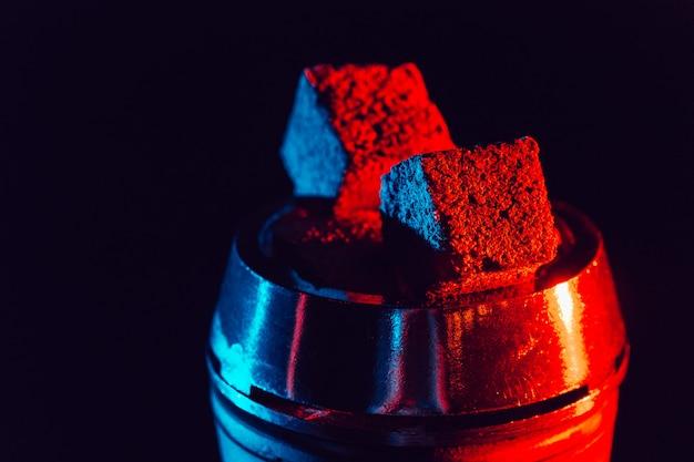 Carboni rossi caldi per narghilè in una ciotola di metallo