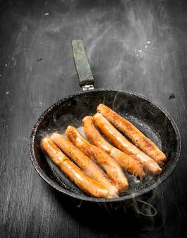 Salsicce calde in padella. sulla lavagna nera.