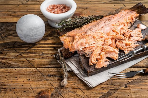 Filetto di salmone affumicato a caldo su una tavola di legno. fondo in legno. vista dall'alto. copia spazio.