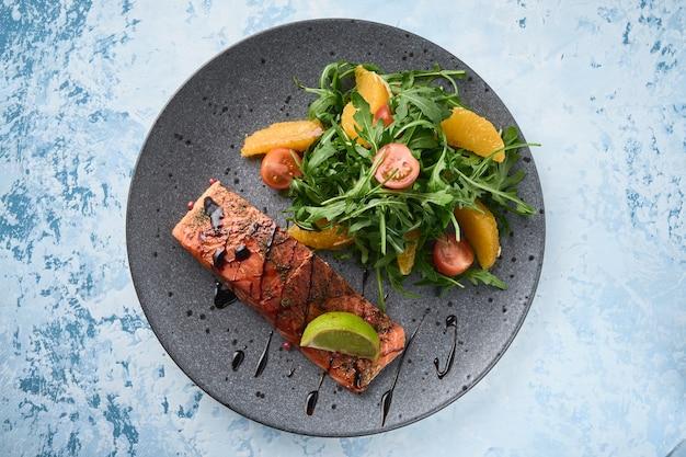 Salmone affumicato caldo con pomodorini insalata di rucola e arancia mangiare sano vista dall'alto