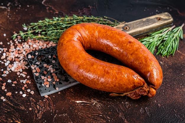 Salsiccia affumicata calda su una mannaia rustica da macellaio con erbe. sfondo scuro. vista dall'alto.