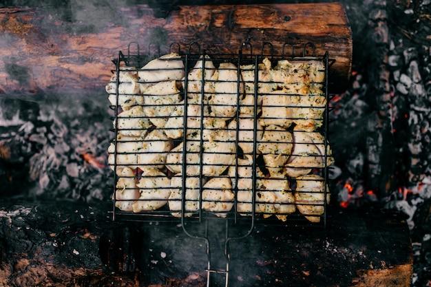 Pezzi di pollo affumicati caldi a carbone e legna bruciata.