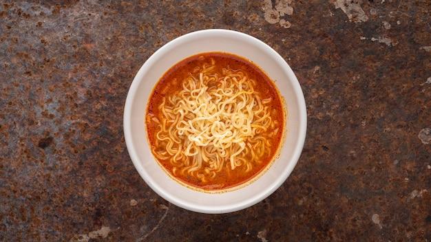 Zuppa di noodle calda e acida, sapore di gamberetti tom yum in ciotola di ceramica bianca su sfondo arrugginito, tom yum goong, tom yum kung, cibo tailandese