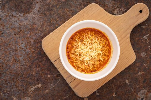 Zuppa di noodle calda e acida, sapore di gamberetti tom yum in ciotola di ceramica bianca su tagliere di legno su sfondo arrugginito, vista dall'alto, tom yum goong, tom yum kung, cibo tailandese