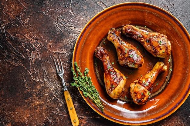 Cosce di pollo bbq calde e piccanti in un piatto. sfondo scuro.