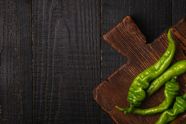 Peperoncini verdi piccanti caldi sul tagliere di legno del teck. vista dall'alto