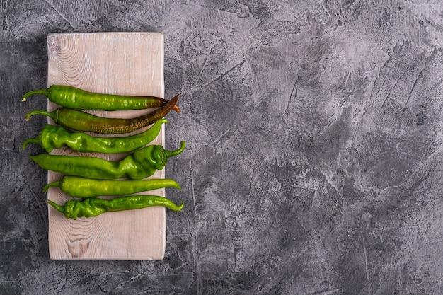 Peperoncini verdi piccanti caldi sul tagliere di legno, tavolo in cemento di pietra, spazio di copia vista dall'alto
