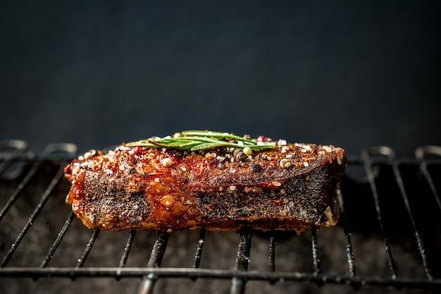 Bistecca piccante alla griglia su un barbecue estivo sui carboni ardenti guarnita decorata con un ramo di rosmarino. cucinare il cibo. avvicinamento