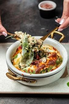 Crepes agli spinaci o frittelle calde con pollo e funghi al forno con formaggio. concetto di cucina, immagine verticale. copia spazio.