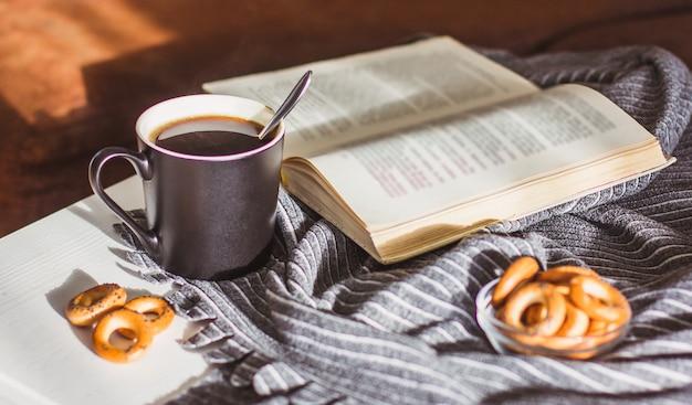 Caffè caldo fumante in una tazza nera, biscotti e un vecchio libro su un tavolo di legno bianco