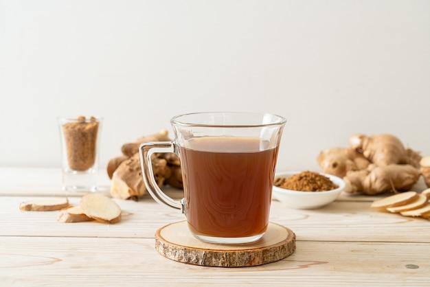 Bicchiere di succo di zenzero caldo e dolce con radici di zenzero - stile di bevanda salutare