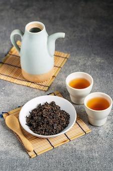 Tè caldo in teiera di vetro e tazza con vapore