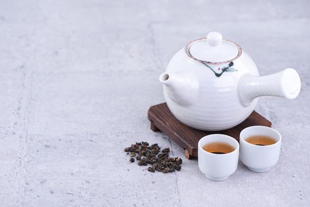 Tè caldo in teiera bianca e tazze su un setaccio su sfondo grigio brillante di cemento, primo piano, concetto di progetto dello spazio della copia.