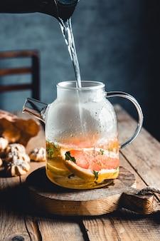 Tè caldo con fette di pompelmo fresco su fondo in legno. bevanda salutare, eco, vegana