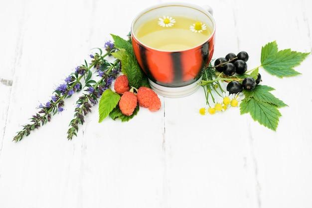Tè caldo su uno sfondo bianco in legno, gli ingredienti per la preparazione di tisane naturali
