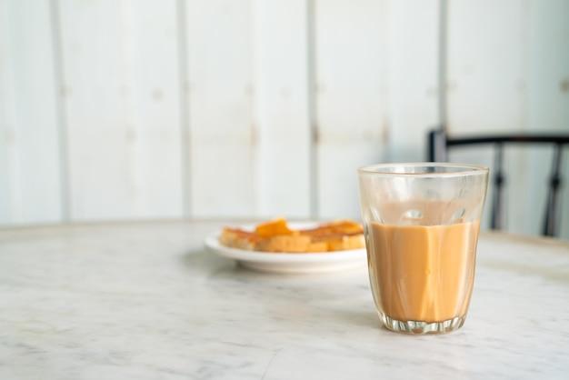 Bicchiere di tè al latte tailandese caldo sul tavolo