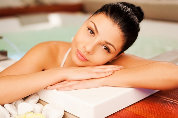 Relax in vasca idromassaggio. attraente giovane donna che si rilassa nella vasca idromassaggio e guarda la telecamera
