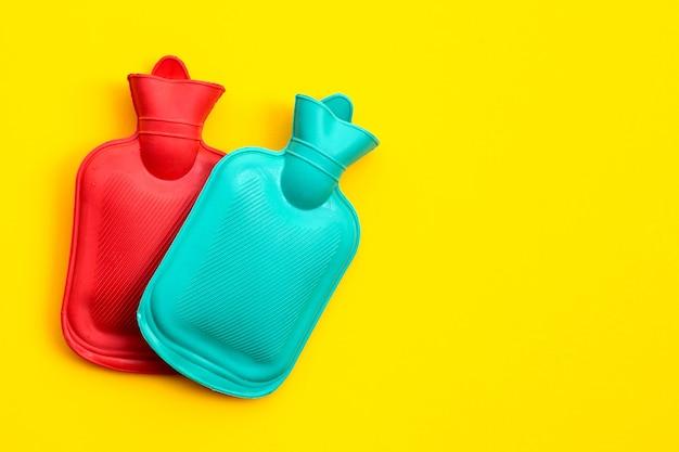 Sacchetti di acqua calda sulla parete gialla. copia spazio