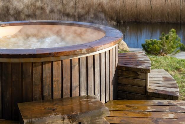Acqua calda vorticosa nella vasca idromassaggio in legno all'esterno.